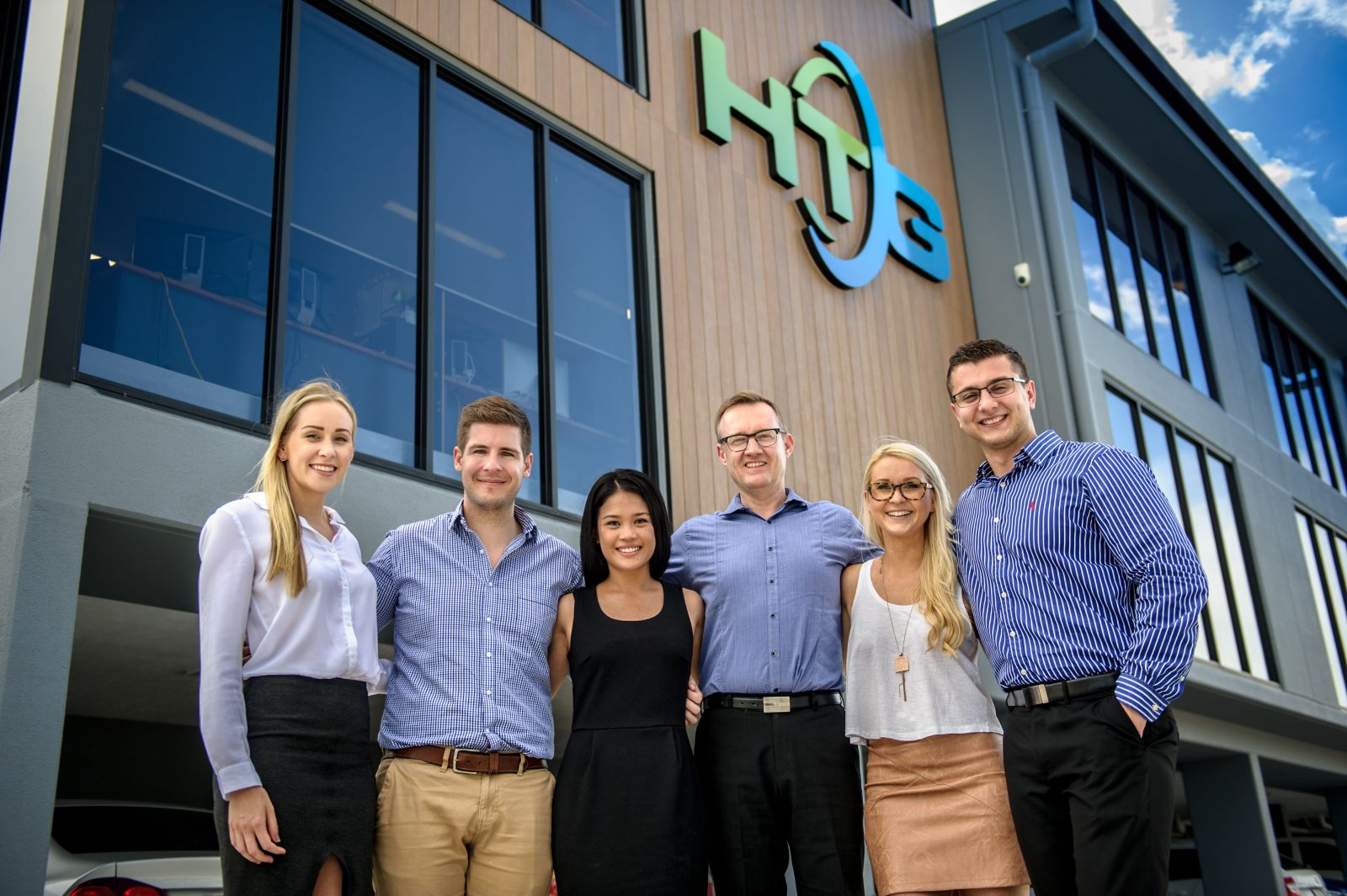 Team in business attire outside of HTG