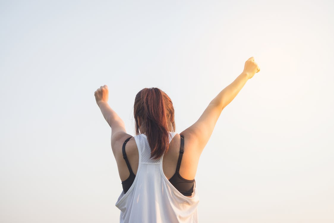 Girl in fitness clothes with arms in the air staying motivated